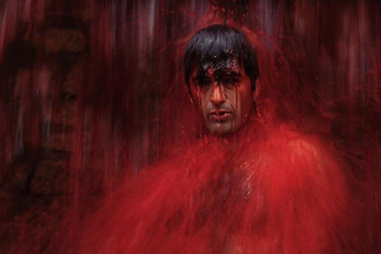 A man takes a red shower.