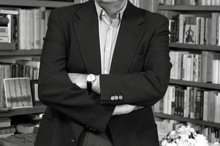 A man stands with folded arms in front of bookshelves