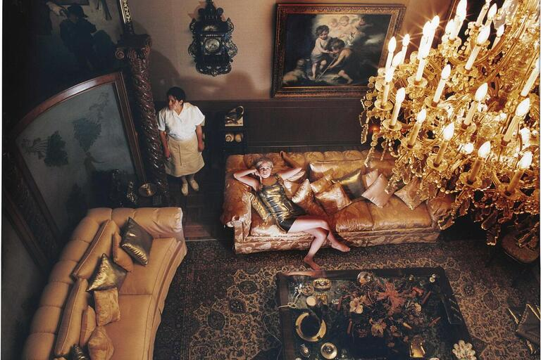 A woman lies on a couch in an opulent room while a maid stands by