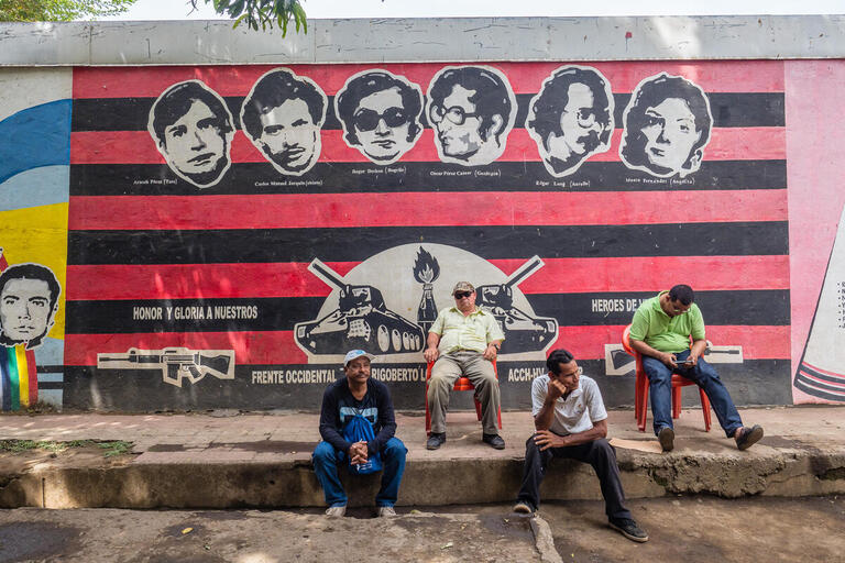 Men sit in front of a black and red Sandinista mural.