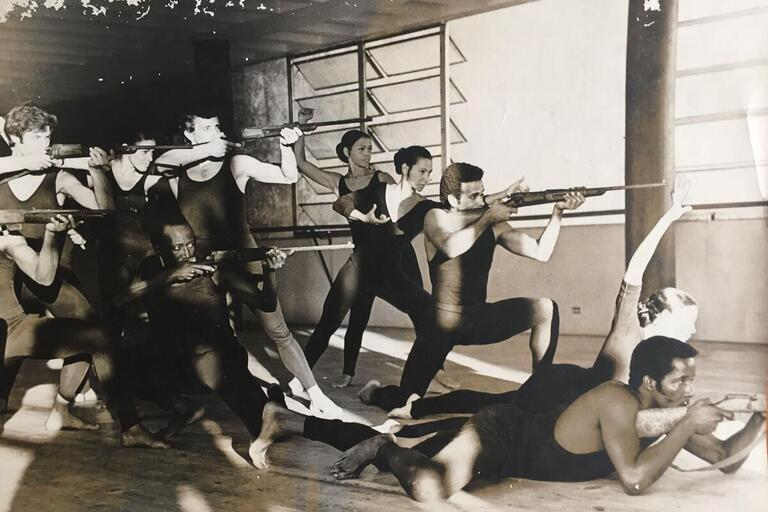 Black and white image of dancers with guns