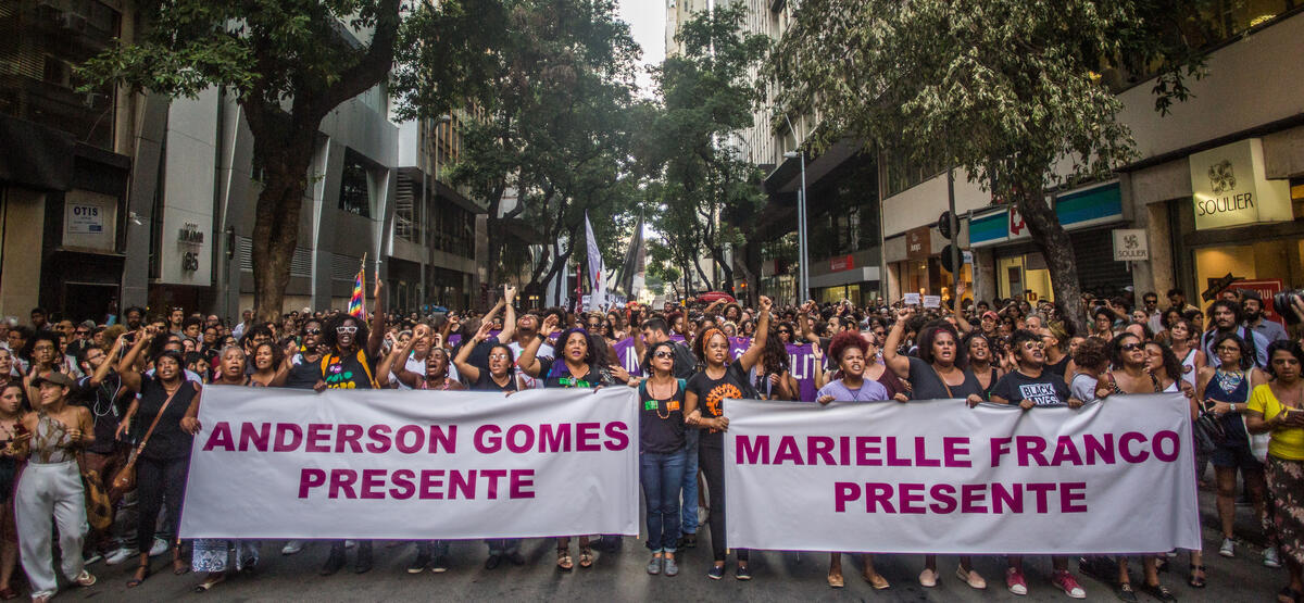 """People marching with posters that read """"Anderson Gomes Presente"""" and """"Marielle Franco Presente"""""""