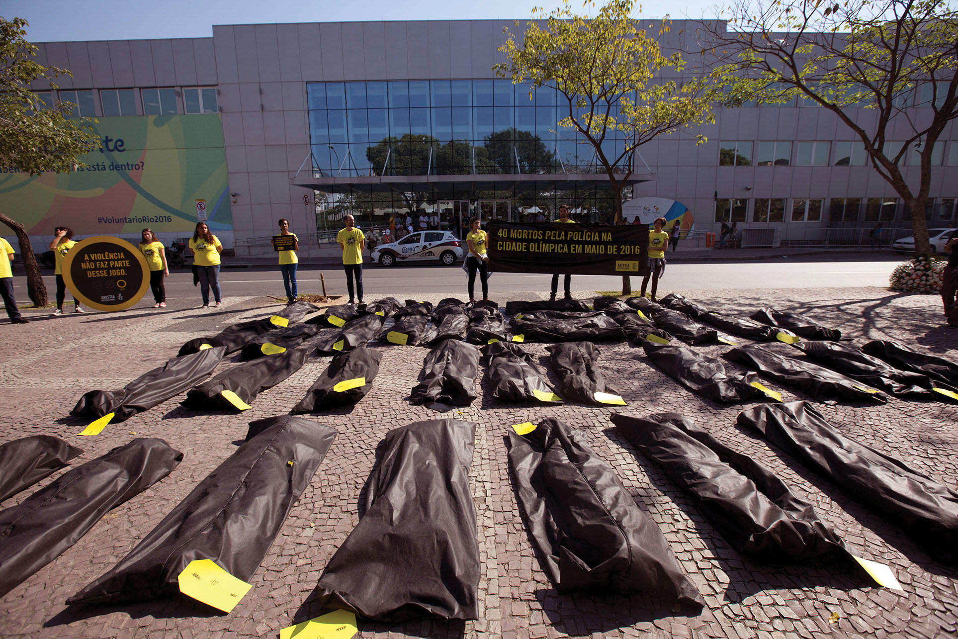 Rows of body bags on the sidewalk are used to represent victims in a protest of police violence in Brazil. (Photo by Silvia Izquierdo/AP Photo.)