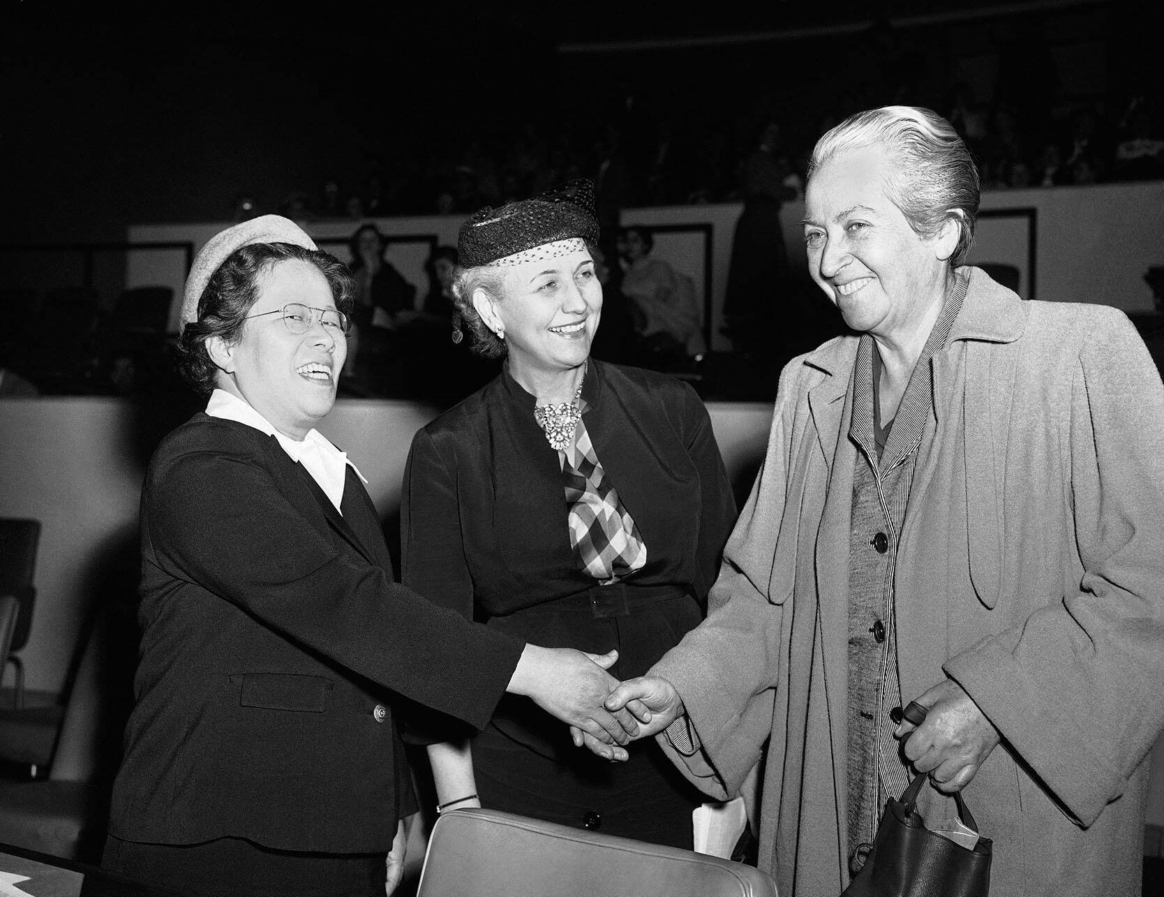 Black and white photo of Gabriela Mistral (right) greeting other attendees at a meeting of the U.N. Commission on the Status of Women in New York, March 1953. (Photo by John Rooney/AP Photo.)