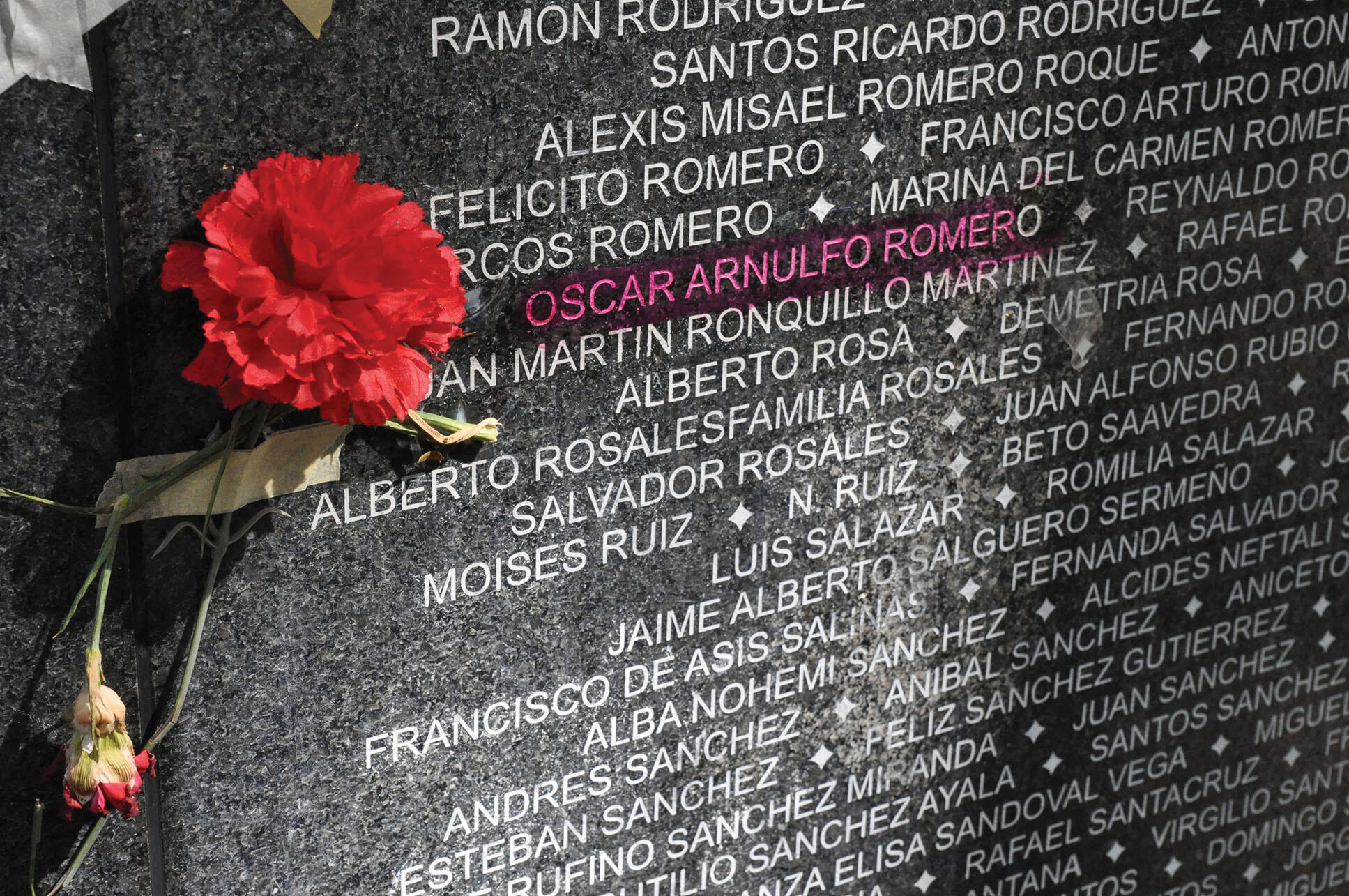 Archbishop Oscar Romero's name highlighted on a black wall memorial listing the names of victims of violence in El Salvador. (Photo courtesy of the Archbishop Romero Trust.)