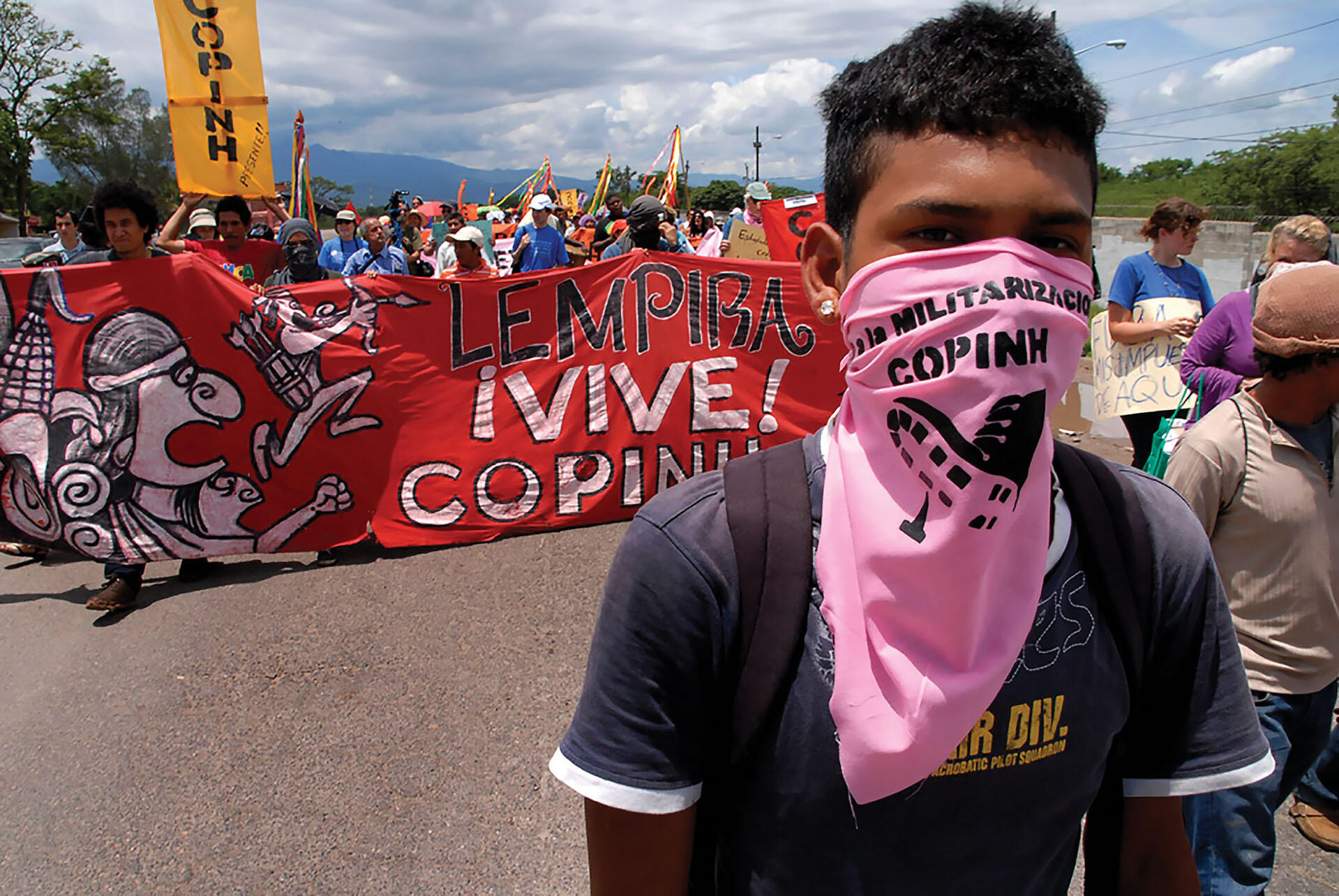 A COPINH protestor wearing a pink bandana as a mask marches in a protest against U.S. military bases in Honduras. (Photo by Felipe Canova.)