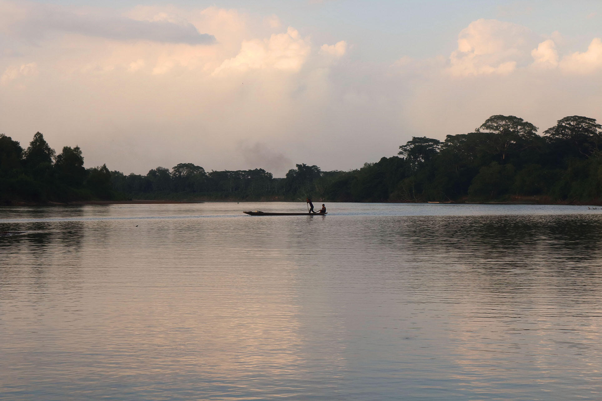A boat with two men crosses the calm waters of Río Patuca in an indigenous bioreserve in Honduras.  (Photo by Marcio Martínez.)