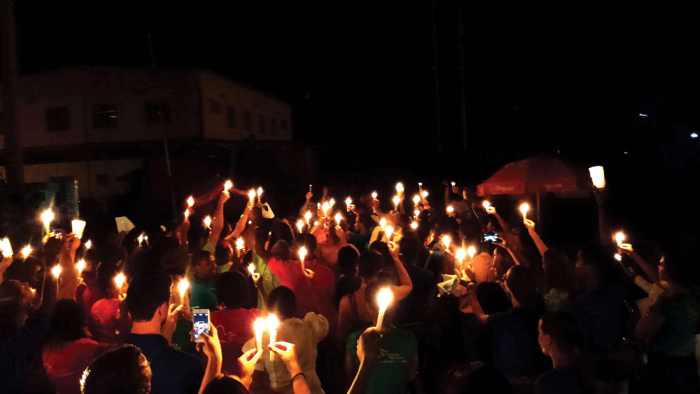 A candlelit procession for a Border of Lights commemoration marches toward the river crossing in Dajabón. (Photo by Edward Paulino.)