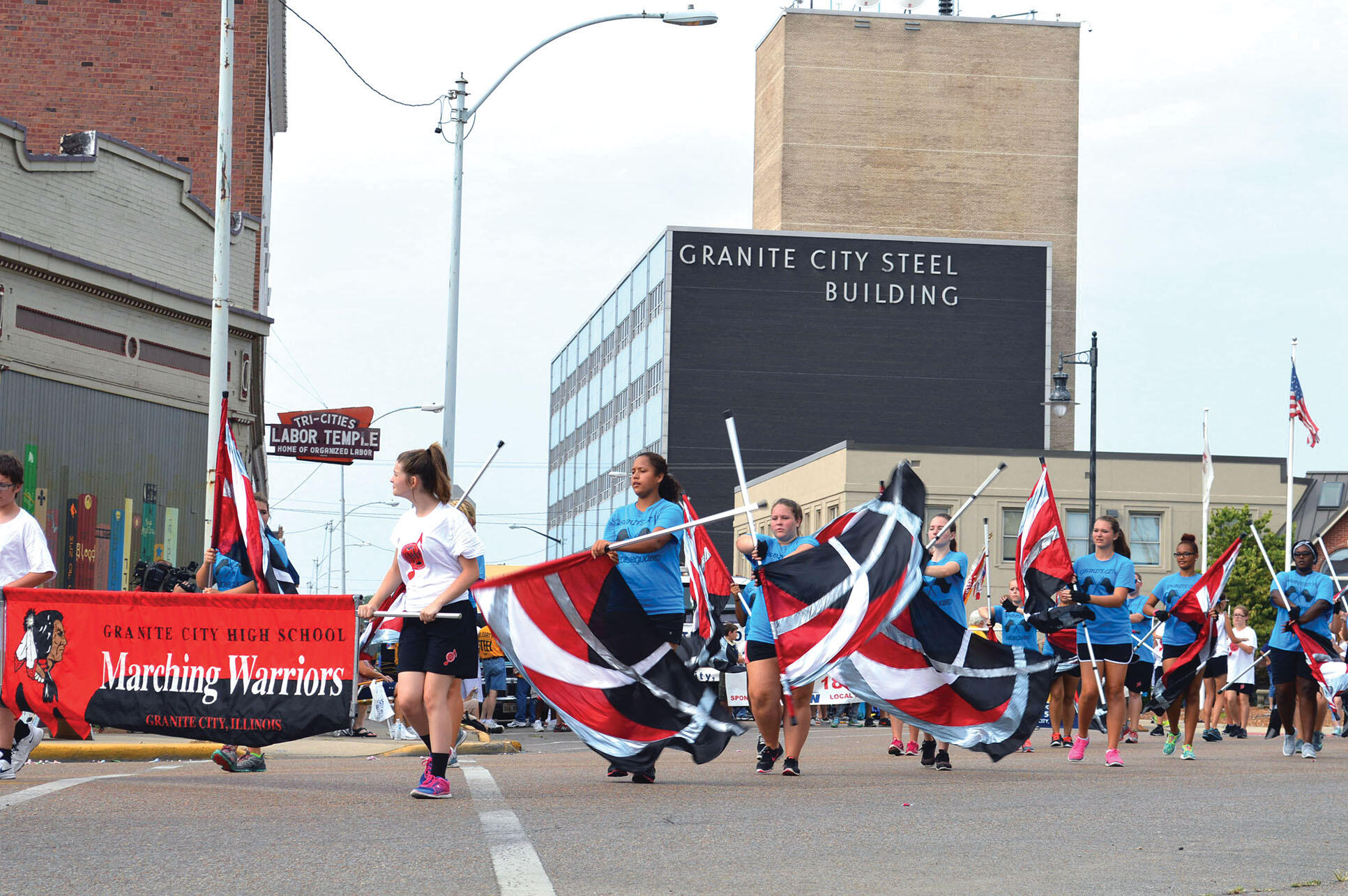 A color guard with flags but no uniforms marches in the 2015 Labor Day parade past the local union hall and the Granite City Steel Building. (Photo by Doug May.)