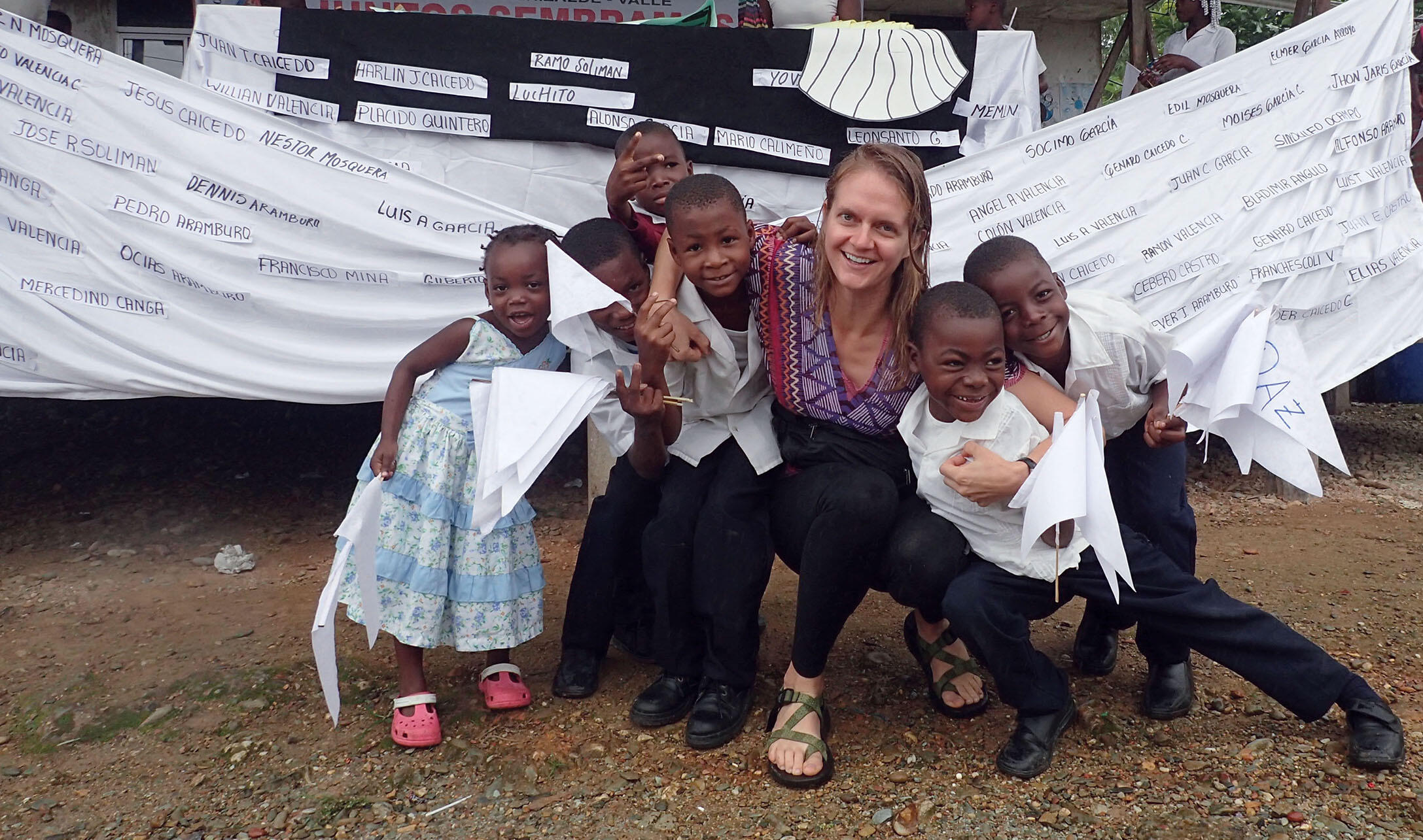 Author Lauren Withey with a group of Afro-Colombian children after a peace march with a banner bearing the names of local victims of the conflict. (Photo courtesy of Lauren Withey.)