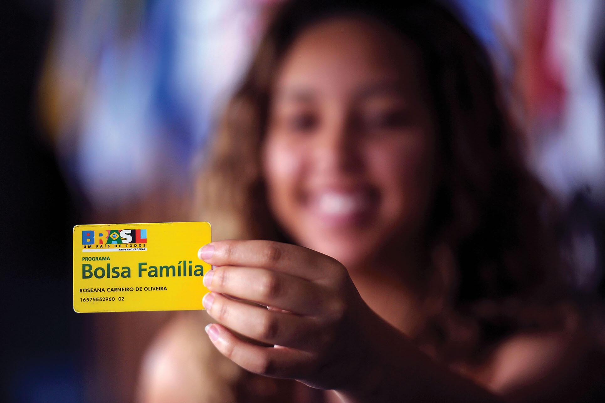 A woman holds up a Brazilian Bolsa Familia identification card in 2014. (Photo courtesy of Senado Federal do Brasil.)