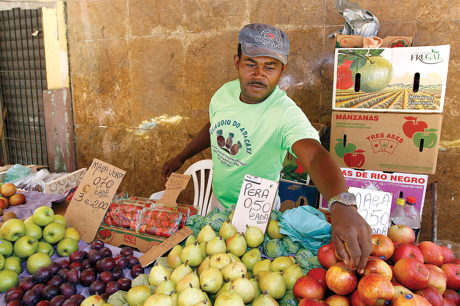 a fruit vendor sets up a stand on the street.
