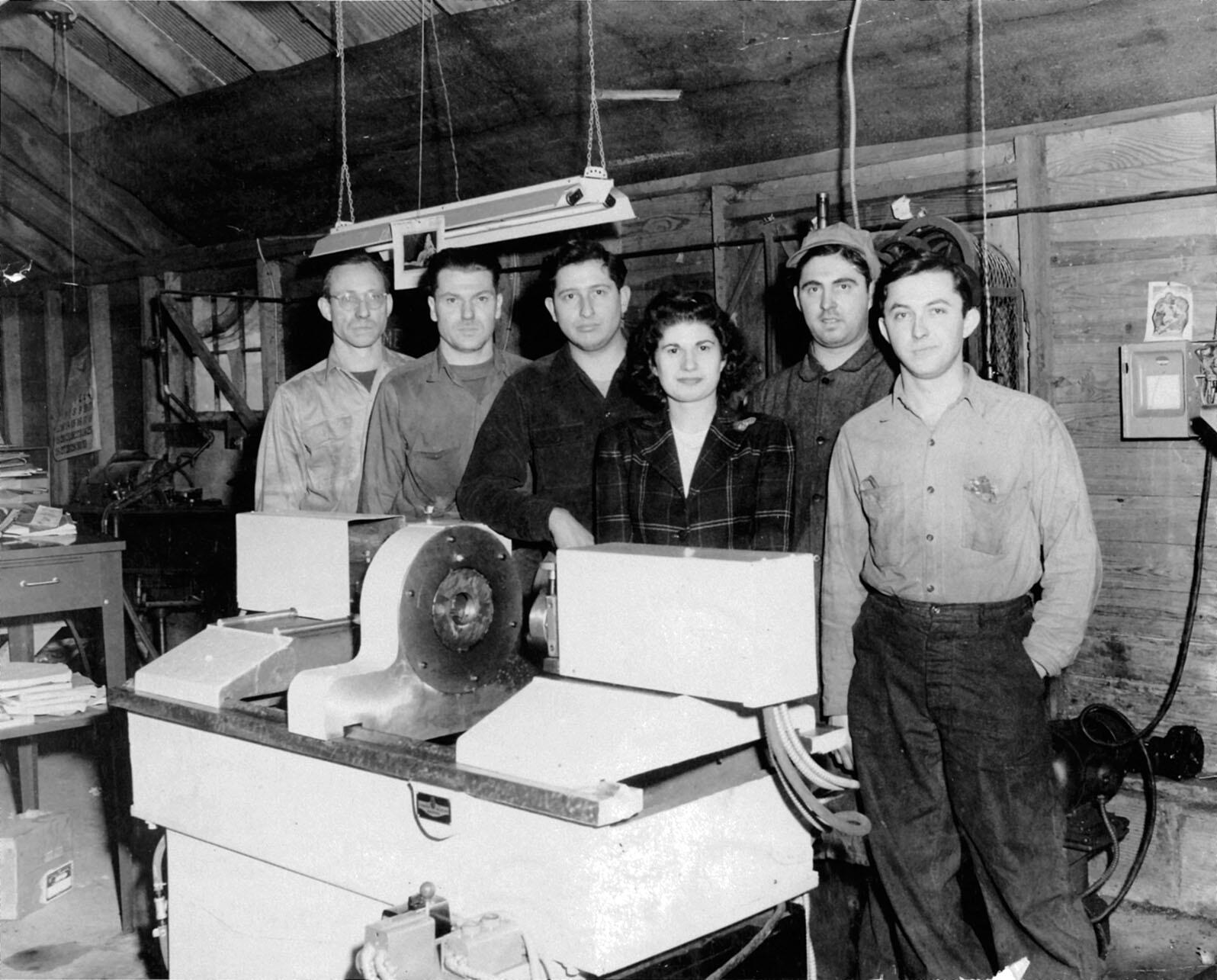 In a converted barn, Stan Ovshinsky (third from left) and his crew pose with his newly invented Benjamin Automatic Lathe in 1946. (Photo courtesy of Lillian Hoddeson and Peter Garrett.)