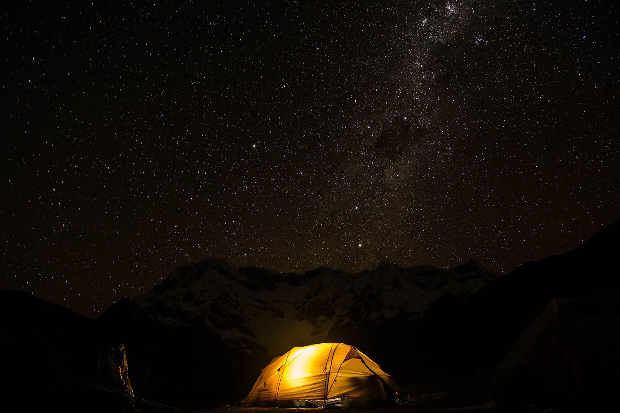 Photo of an illuminated tent under the stars; one of the many camps of the research team, at Upispampa. (Photo by Emma Steigerwald.)