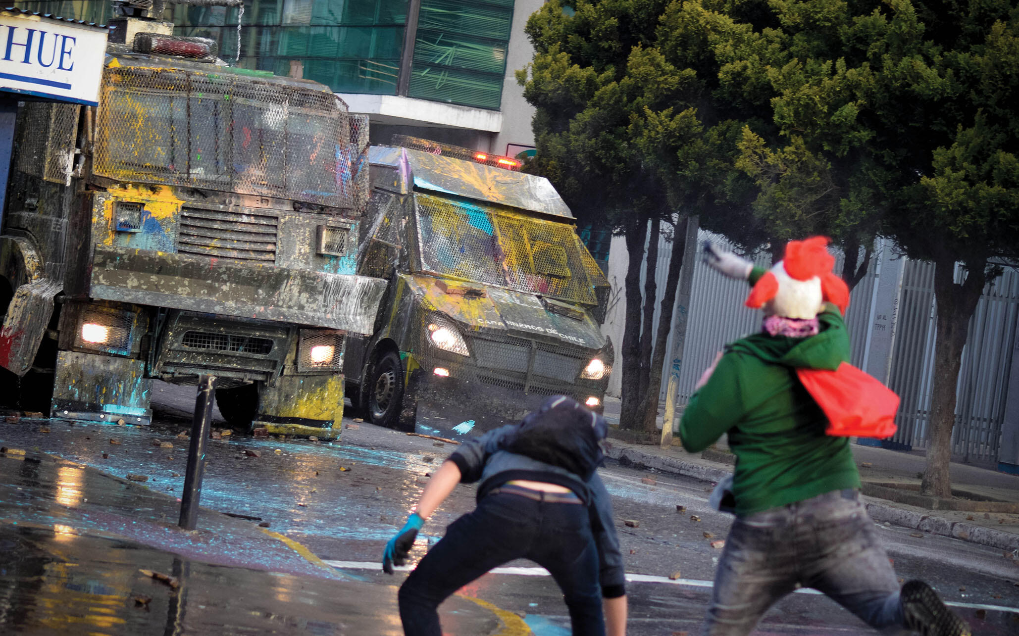 Demonstrators throw paint at police vehicles in Santiago, November 2019. (Photo by cameramemories.)