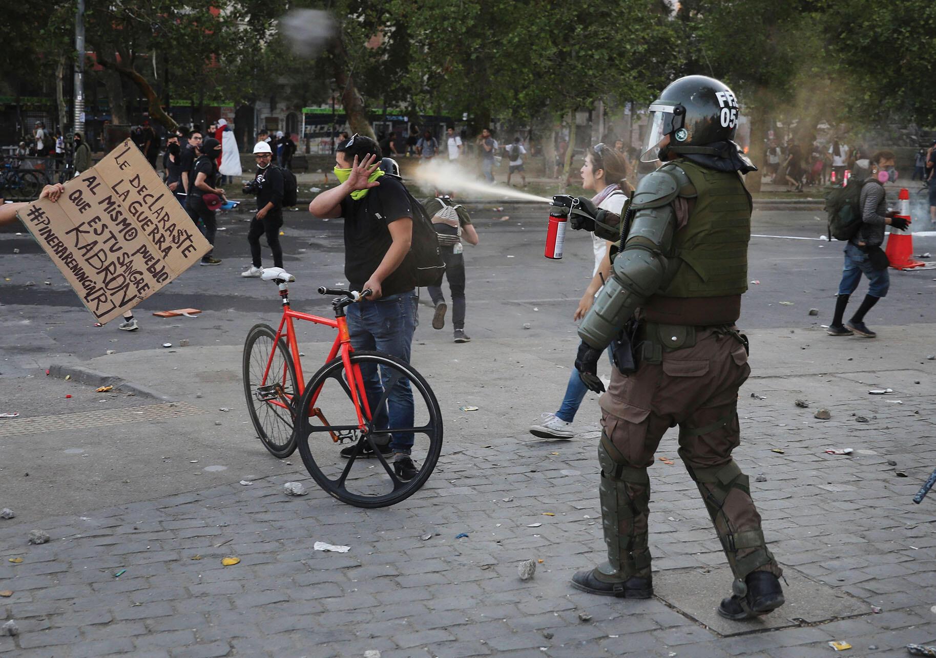 A Chilean carabinero pepper-sprays a demonstrator in Santiago, October 2019. (Photo by Rodrigo Abd/AP Photo.)