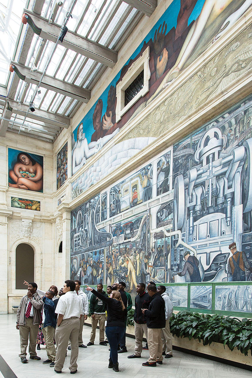 """A docent points out parts of """"Detroit Industry"""" to local students visiting the Detroit Institute of Art's Rivera Court. (Photo © 2017 Detroit Institute of Arts.)"""