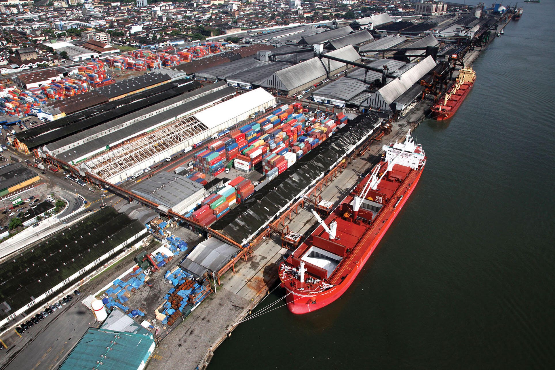 The busy port of Santos, Brazil, with ships being loaded by overhead cranes from a large storage facility for shipping containers.. (Photo courtesy of the Program for Accelerated Growth PAC.)