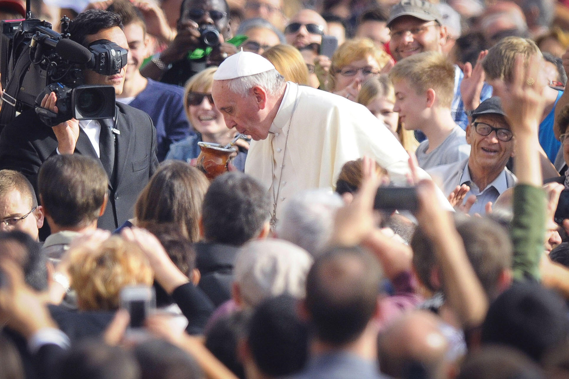 Pope Francis sips from a mug of mate offered by a pilgrim in St. Peter's Square. (Photo from Associated Press.)