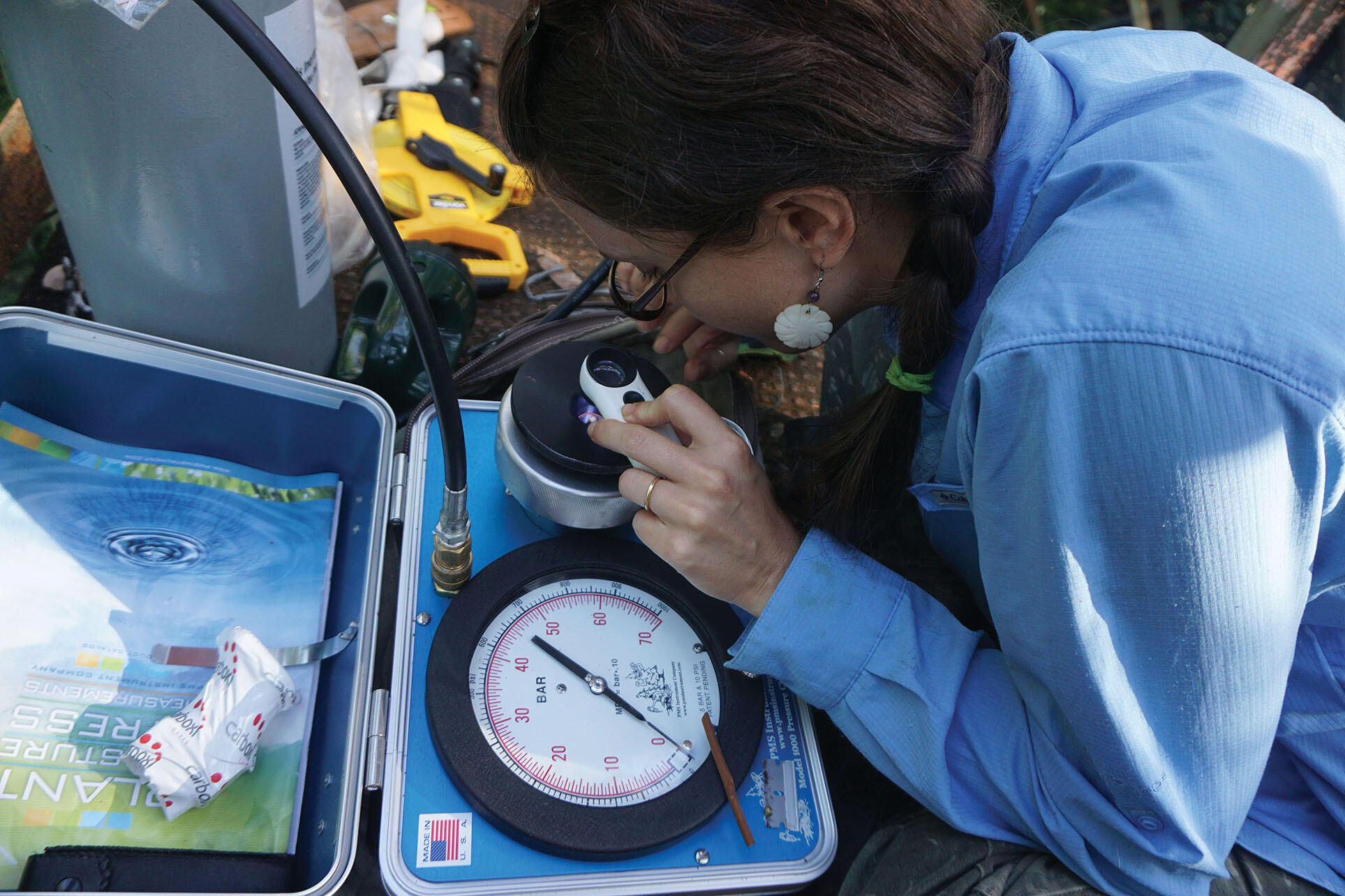 Clarissa Fontes examines her readings as she measures leaf water potential in the Amazon. (Photo courtesy of Kolby Jardine.)