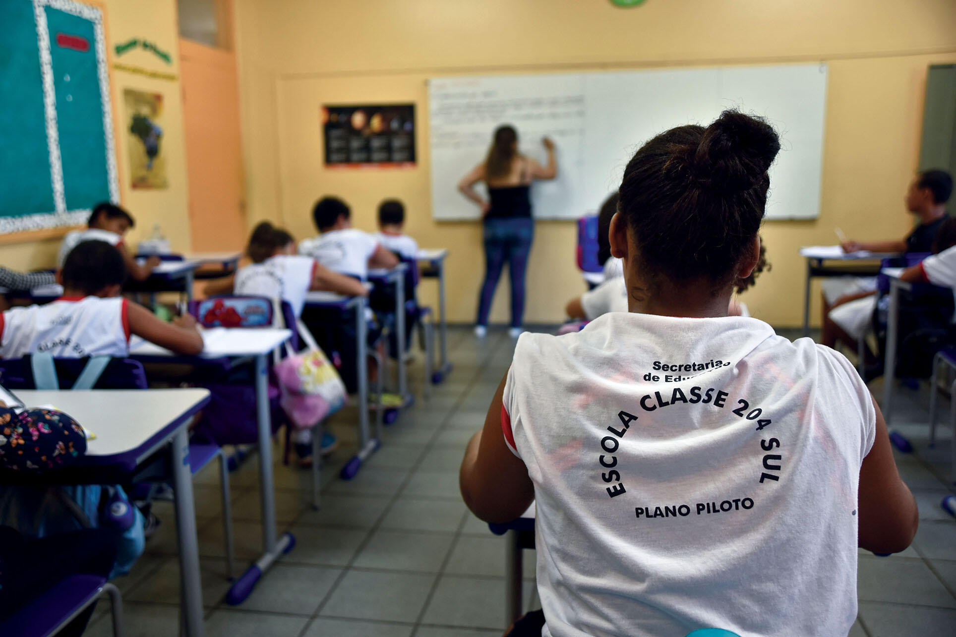 A young Afro-Brazilian woman sits in a class of students participate in a pilot program that supports nutrition, transportation, and extracurricular activities, July 2017. (Photo by Pillar Pedreira/Agência Senado.)
