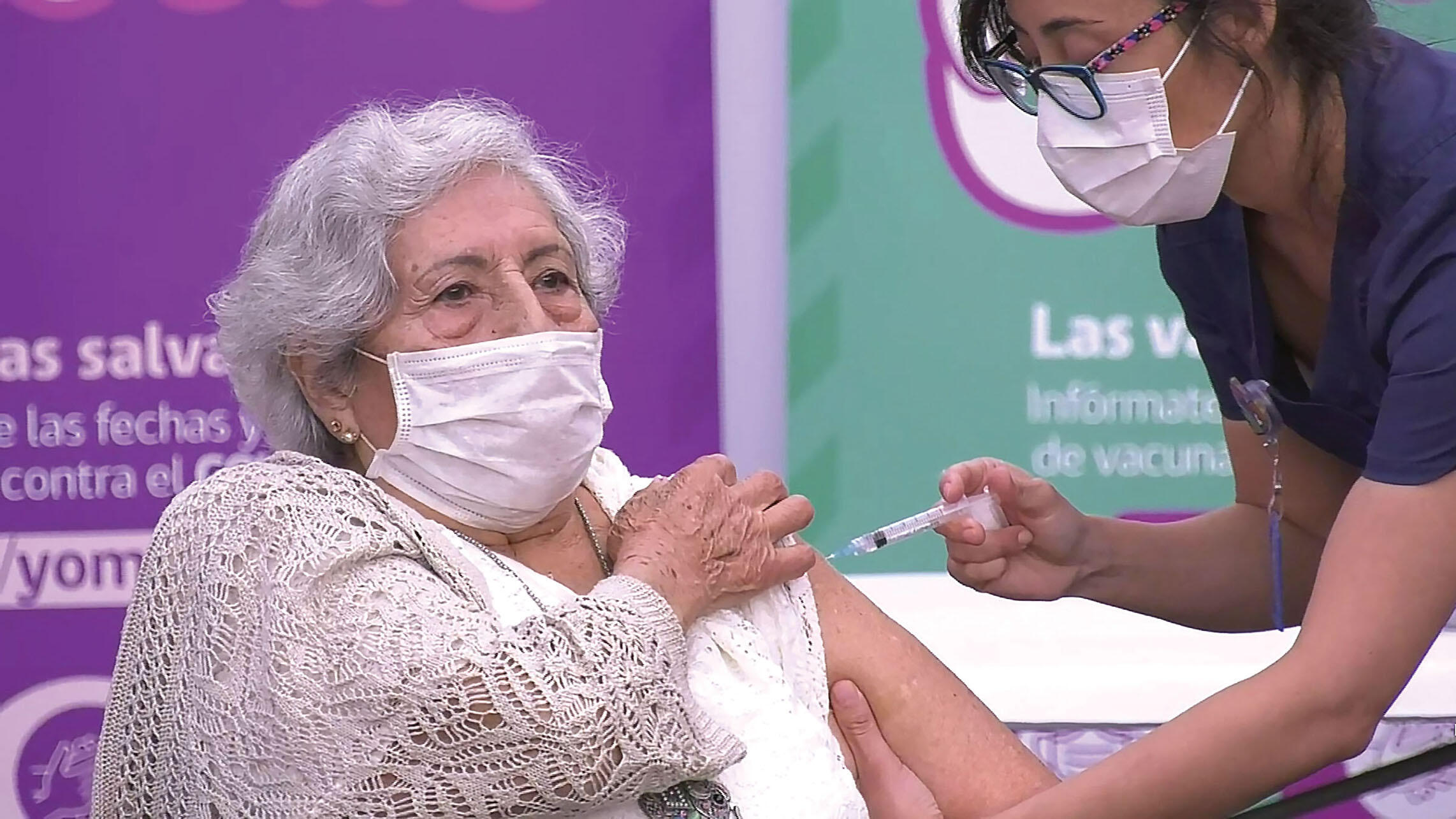 A older woman in a sweater is vaccinated in Santiago, February 2021. (Photo courtesy of Mediabanco Agencia.)