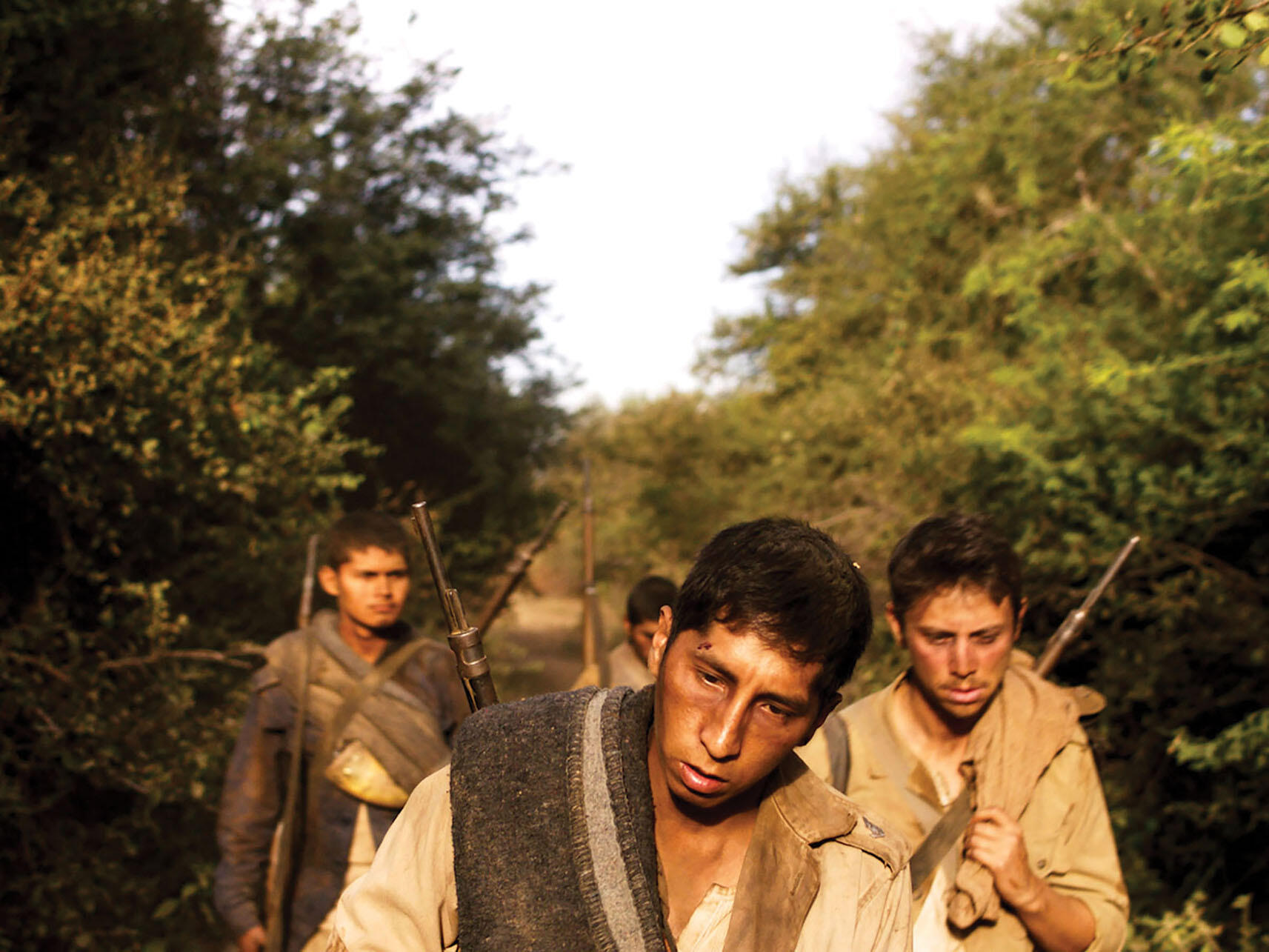 """""""So now tell me, how is your hell where your glory has gone?"""" Somber lyrics from a Bolivian song echo in this still of dejected soldiers marching through the woods from """"Chaco."""" (Image courtesy of Color_Monster, Pasto, and Murillo Cine.)"""