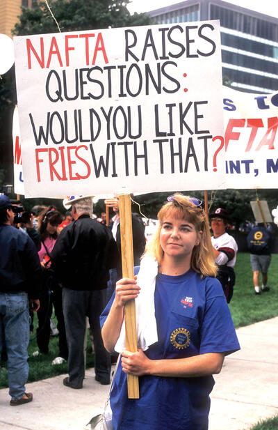 A protester with a sign questioning the quality of jobs created under Nafta. (Photo by Jim West/Alamy Stock Photo.)