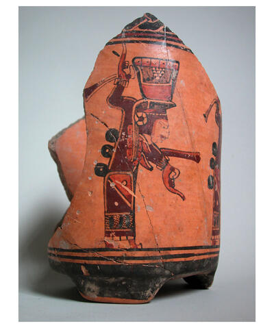 A broken orange and brown pottery urn is decorated with a woman carrying a vessel filled with liquid as part of a ceremony. Ulua Valley, ca. 700-800 CE, from the Museo de San Pedro Sula. (Photo courtesy of Russell Sheptak.)